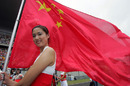 A grid girl waves a Chinese flag on the grid