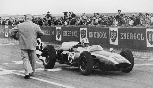 Jack Brabham takes the chequered flag to win