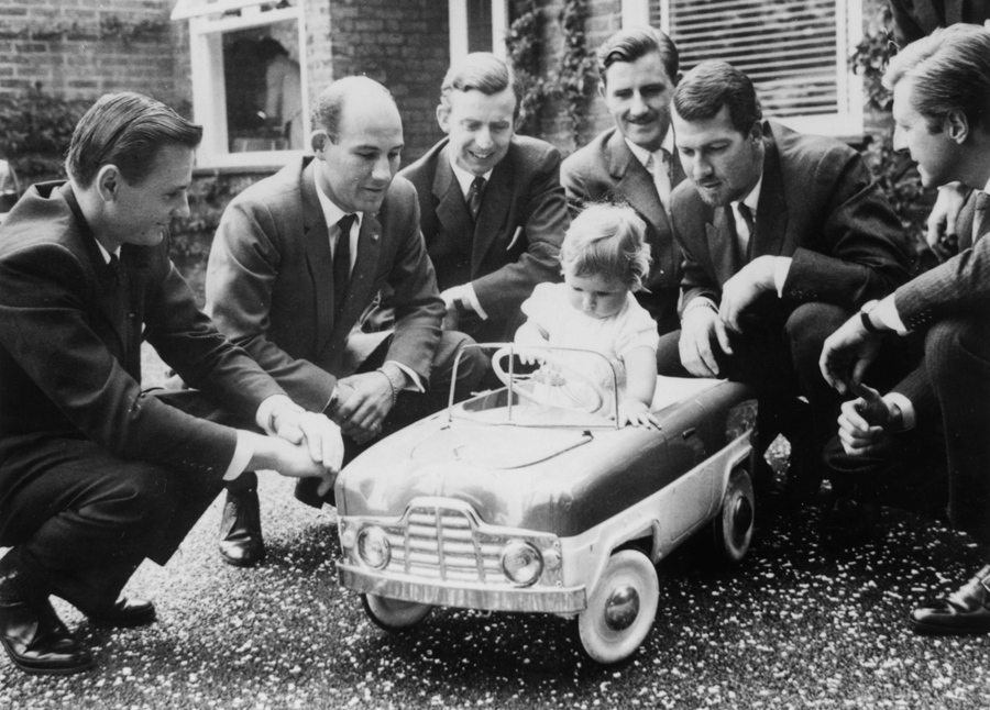 Damon Hill sitting in a toy car at his christening watched by some great names