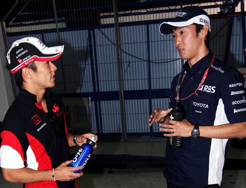 Takuma Sato and Kazuki Nakajima chat in parc ferme