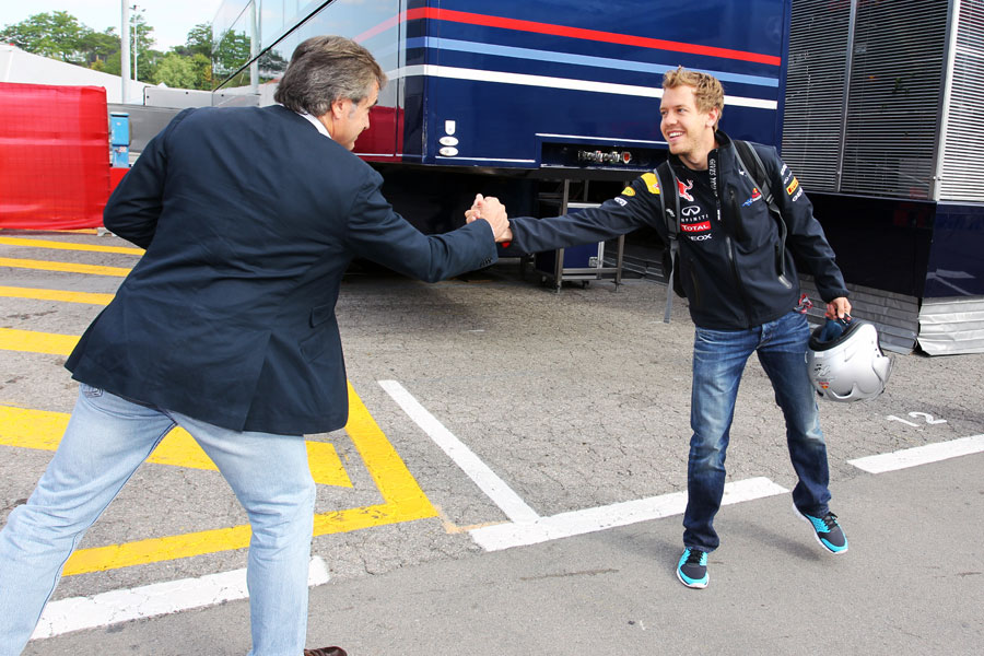 Sebastian Vettel is greeted by Carlos Sainz as he arrives at the circuit