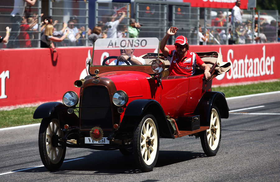 Fernando Alonso waves to his fans on the drivers' parade