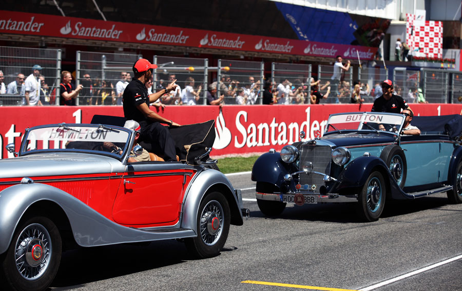 Lewis Hamilton and Jenson Button share a joke on the drivers' parade