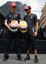 Jenson Button and Lewis Hamilton pose with their diamond-encrusted helmets