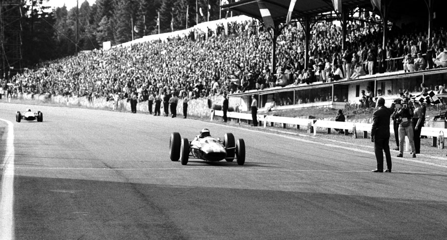 Jim Clark takes the chequered flag after passing the coasting Bruce McLaren