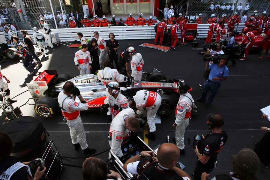 Jenson Button's McLaren is serviced on the grid during the red flag period