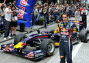 Sebastien Buemi poses for photographers beside Formula One machine of Red Bull in Japan