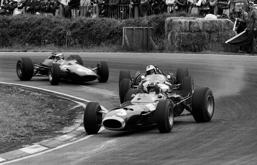 Graham Hill slides his BRM as he tries to hold off John Surtees and Jim Clark