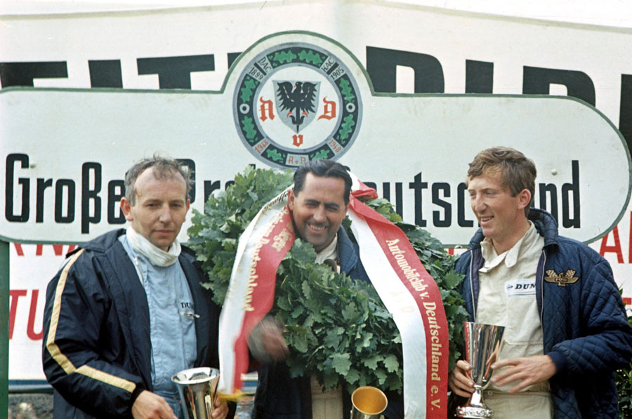 Jack Brabham celebrates his victory on the podium with John Surtees and Jochen Rindt