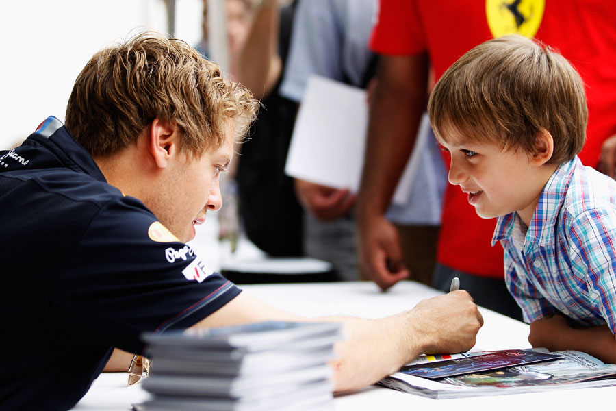 Sebastian Vettel signs his autograph for a young fan