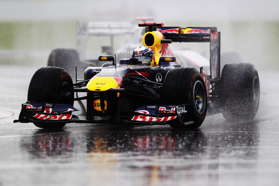 Sebastian Vettel splashes through the standing water