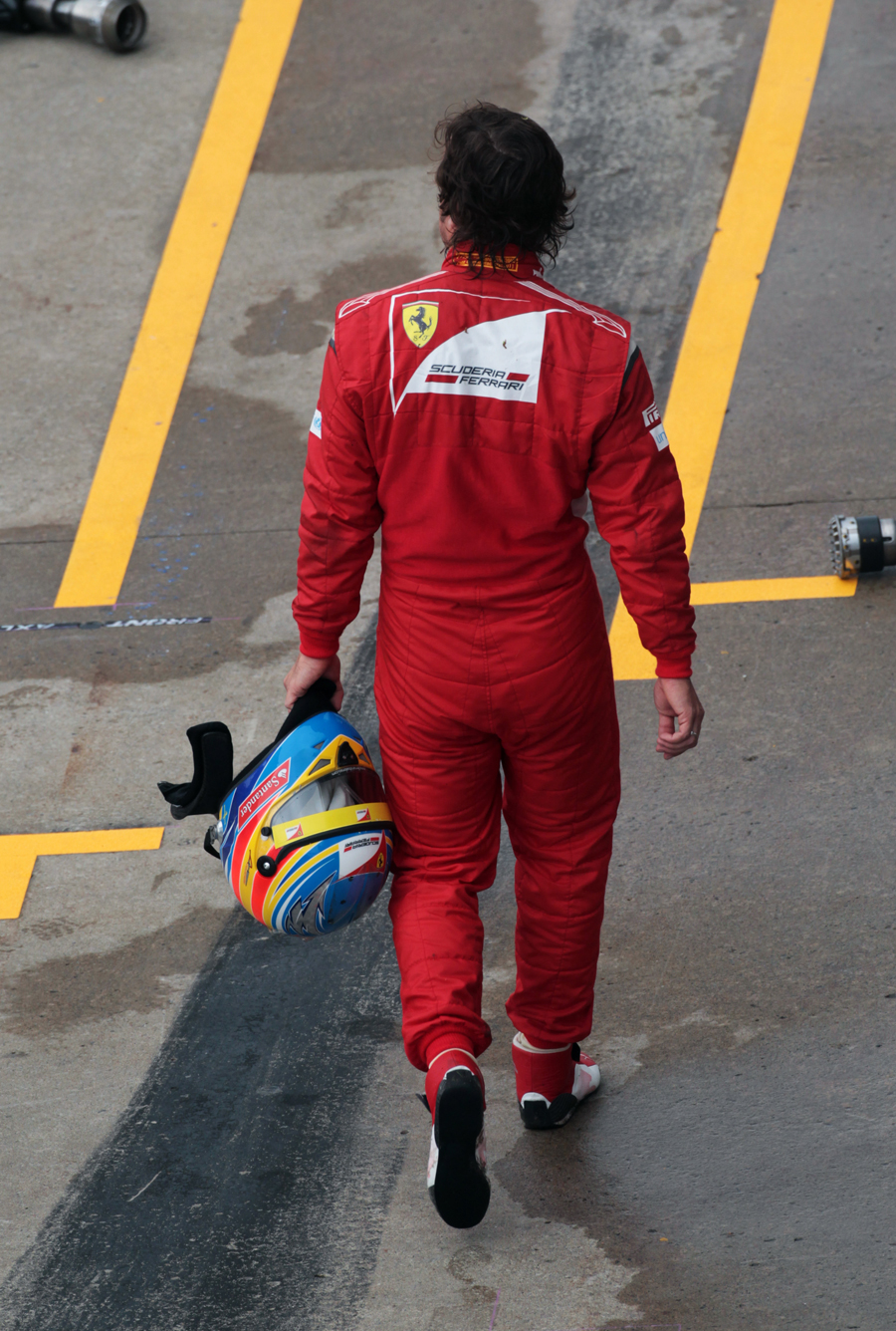 Fernando Alonso trudges back to the pits after his retirement