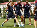 Sebastian Vettel tackles footballer Thierry Henry during a training session with the New York Red Bulls