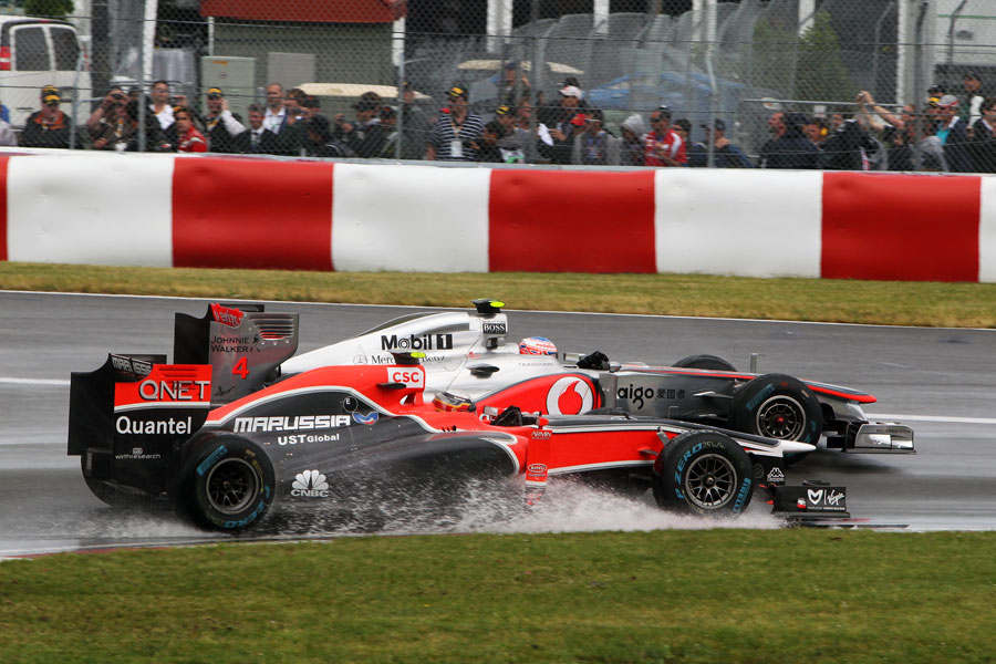 Jenson Button goes round the outside of Jerome d'Ambrosio