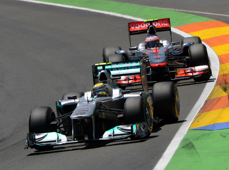 Nico Rosberg holds off Jenson Button early in the race
