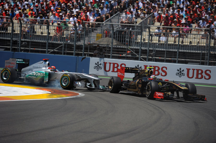 Michael Schumacher clips his front wing against Vitaly Petrov's Renault