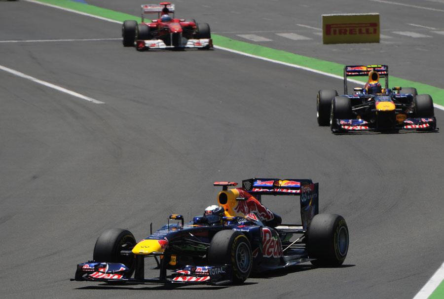 Sebastian Vettel leads Mark Webber and Fernando Alonso into turn two