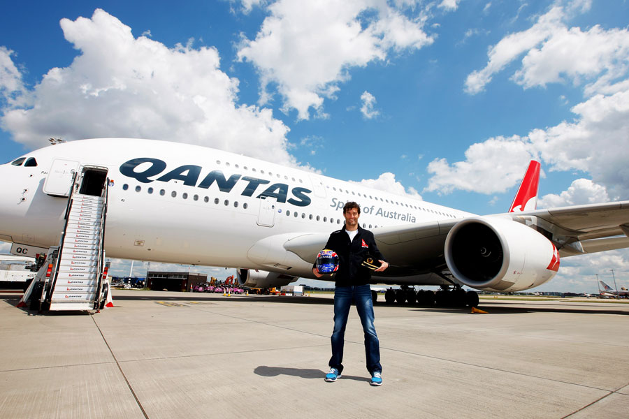 Mark Webber poses for a photo in front of an Airbus A380 after an announcement that he will train to become a pilot with the help of Qantas