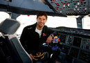 Mark Webber poses for a photo in the cockpit of an Airbus A380 after an announcement that he will train to become a pilot with the help of Qantas