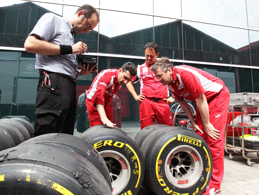 Fernando Alonso's race engineer Andrea Stella examines tyres with Ferrari technical director Pat Fry