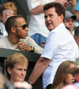 Lewis Hamilton chats with manager Simon Fuller on Centre Court at Wimbledon