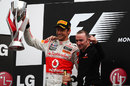 Jenson Button celebrates his remarkable victory on the podium with Paddy Lowe