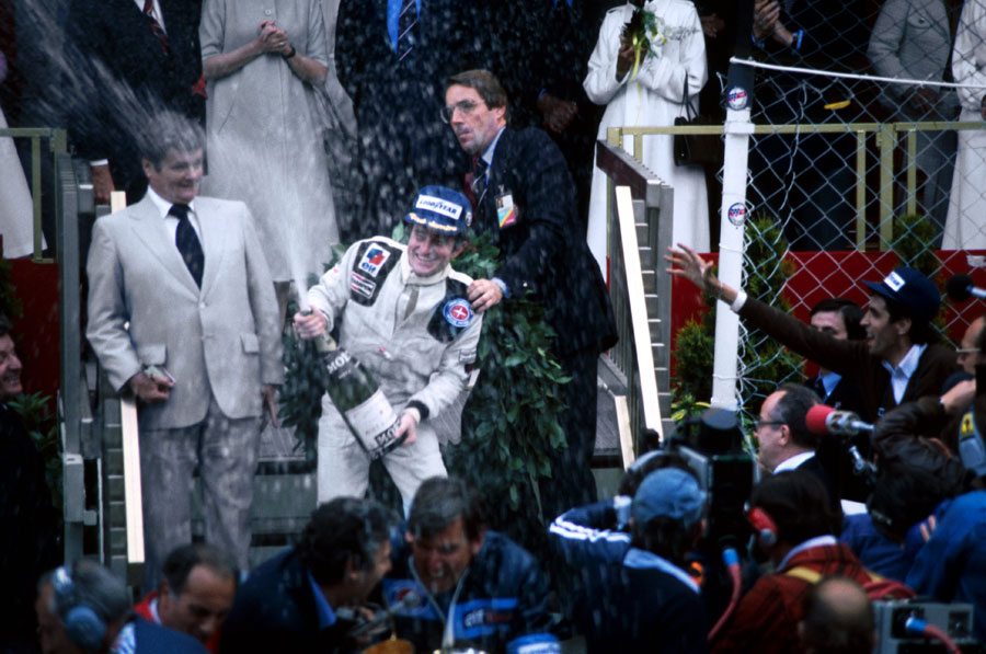 Patrick Depailler celebrates his first grand prix victory on the podium at Monaco