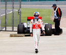 Jenson Button walks away from his McLaren after the botched tyre change which ended his race
