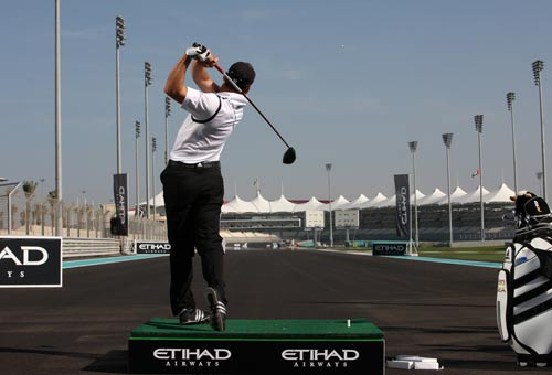 Golfer Sergio Garcia tees off on the start-finish straight at the Abu Dhabi Grand Prix circuit