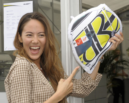 Jessica Michibata smiles while showing off a Jenson Button helmet-style cushion
