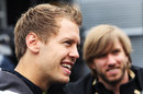 German drivers Sebastian Vettel and Nick Heidfeld joke in the paddock on Thursday morning