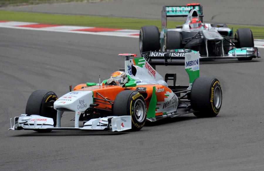 Adrian Sutil leads Michael Schumacher on track