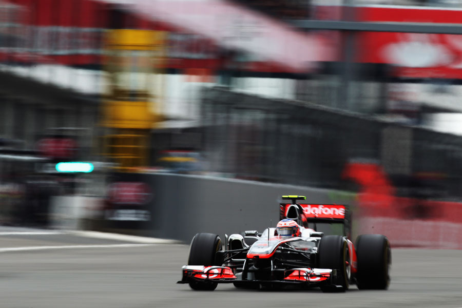 Jenson Button speeds past the pit exit