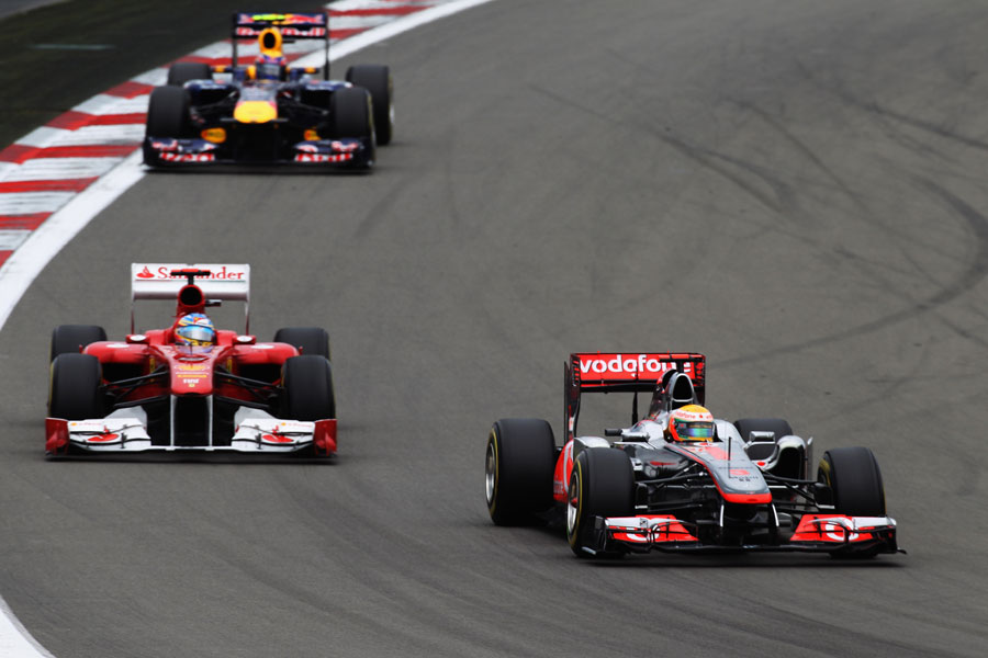Lewis Hamilton defends from Fernando Alonso, with Mark Webber trying to keep pace