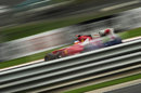 Fernando Alonso flashes past the guardrails in his Ferrari