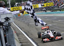 Jenson Button crosses the line to take victory