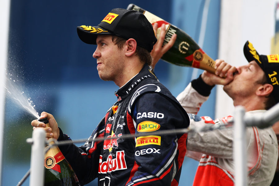 Sebastian Vettel sprays champagne on the podium after coming second