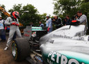 Michael Schumacher assess the rear of his Mercedes after retiring with a gearbox problem