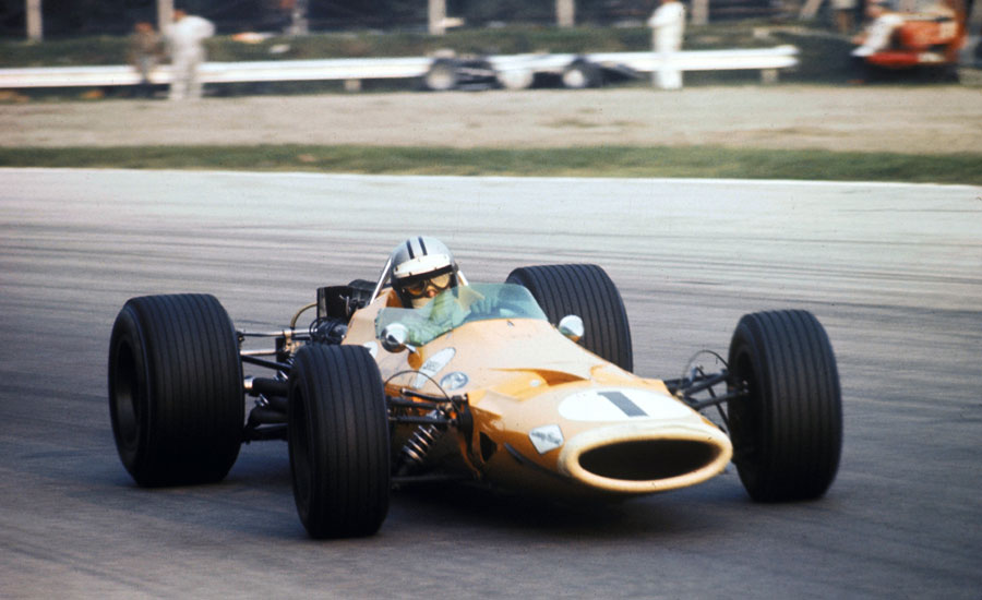 Denny Hulme passes a stricken car on the outside of Parabolica