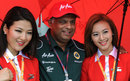 Tony Fernandes poses with Air Asia stewardesses outside the Lotus garage, Malaysian Grand Prix, Sepang, April 10, 2011