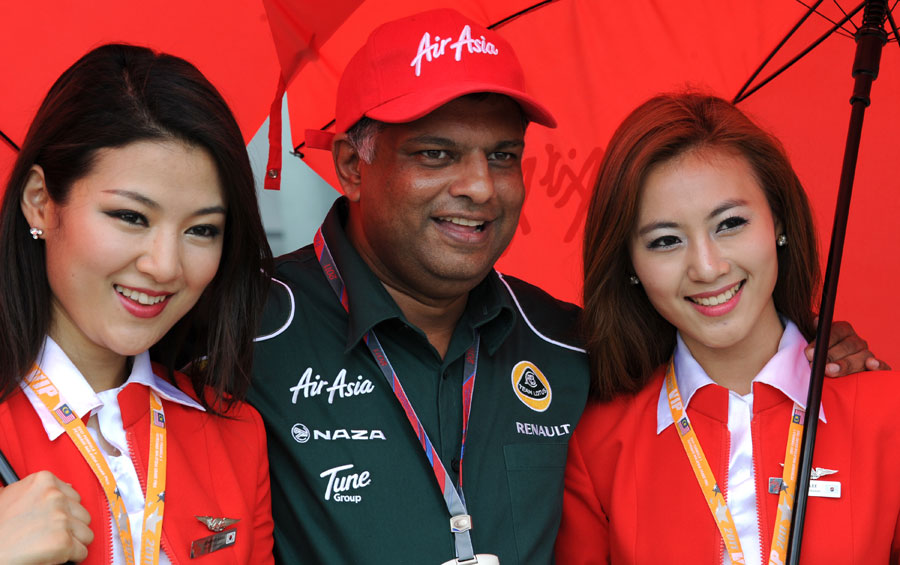Tony Fernandes poses with Air Asia stewardesses outside the Lotus garage