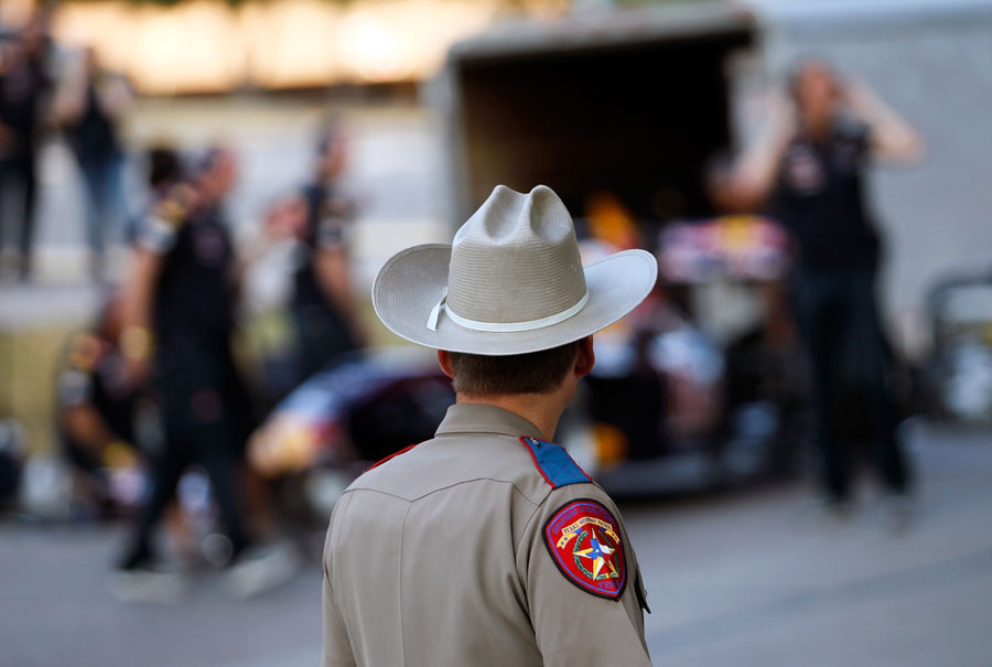A Texas state trooper looks on as David Coulthard prepares to drive the Red Bull Show Car in front of the Texas Capitol building in Austin