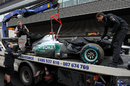 Michael Schumacher's car is towed away after his crash at the start of Q1