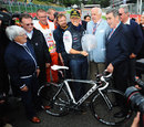 Michael Schumacher is presented with a road bike by cycling legend Eddy Merckx on the 20th anniversary of his GP debut