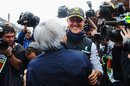 Michael Schumacher is greeted by Bernie Ecclestone on the 20th anniversary of his GP debut