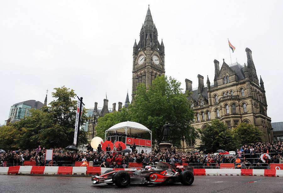 Jenson Button passes Manchester Town Hall on a domestration run