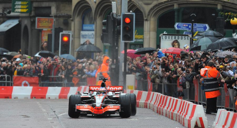 Jenson Button gets the power down on the wet streets during his demonstration run