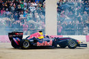 Mark Webber does donuts for the fans after driving his Red Bull F1 car through the city streets of Cardiff