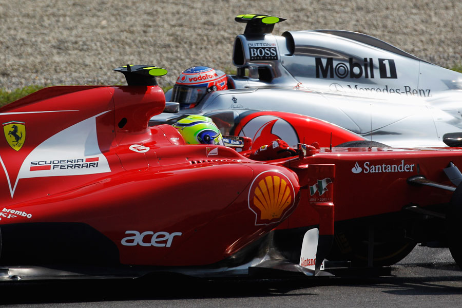 Jenson Button passes the stricken Felipe Massa