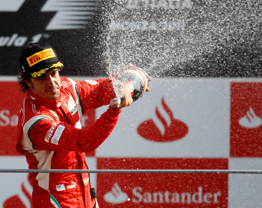 Fernando Alonso celebrates on top of the podium